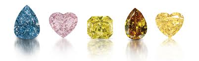 A range of fancy coloured diamonds: blue, pink, and yellow.