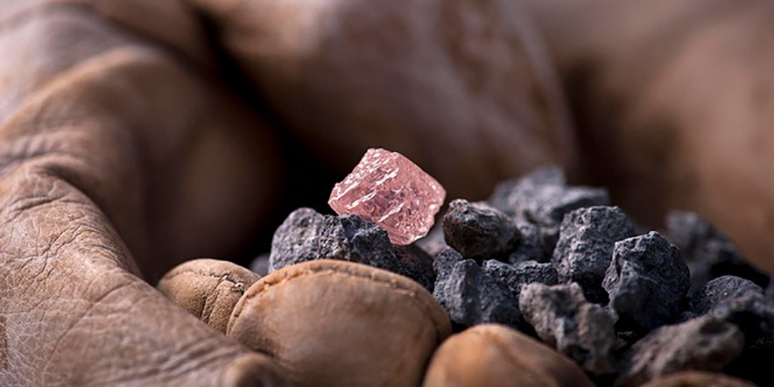 A pink diamond over black stones.