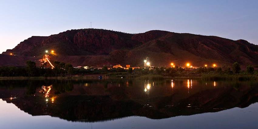 A mining site in the evening and its reflection in the water.