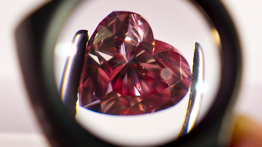 A heart-shaped diamond examined over a lens.