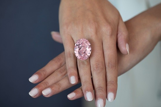 Two hands with a pink diamond on a ring finger.