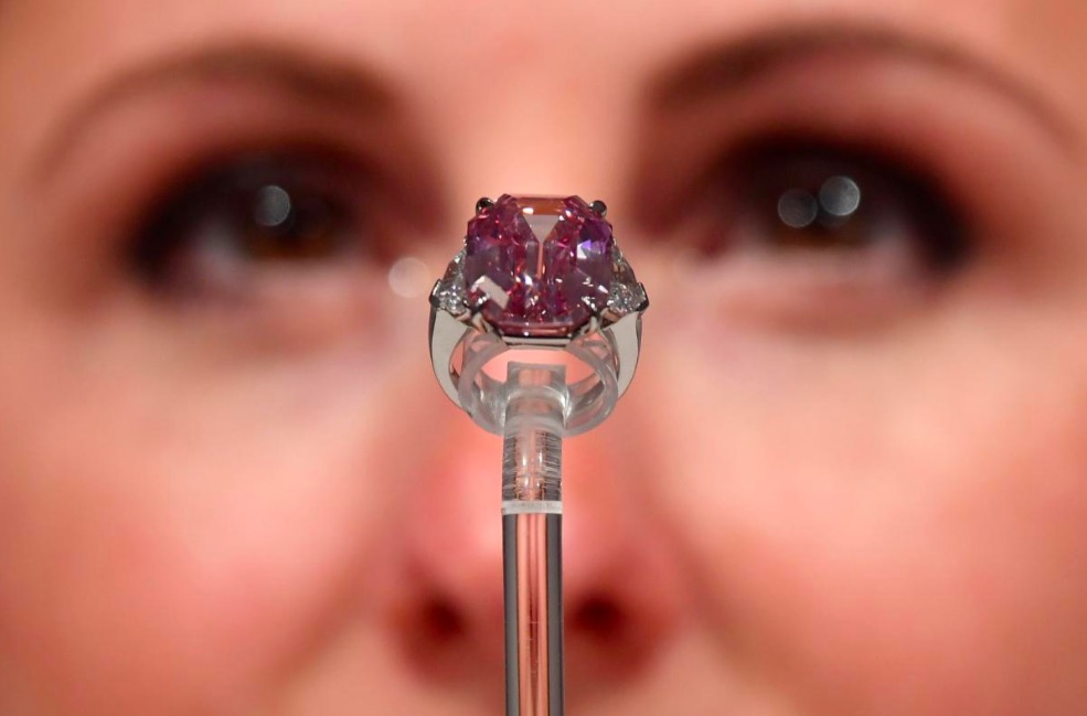 A woman examines a diamond.