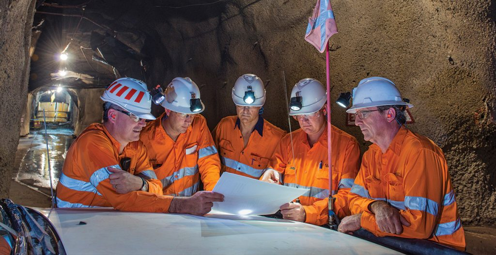Five workers discussing inside argyle mine.