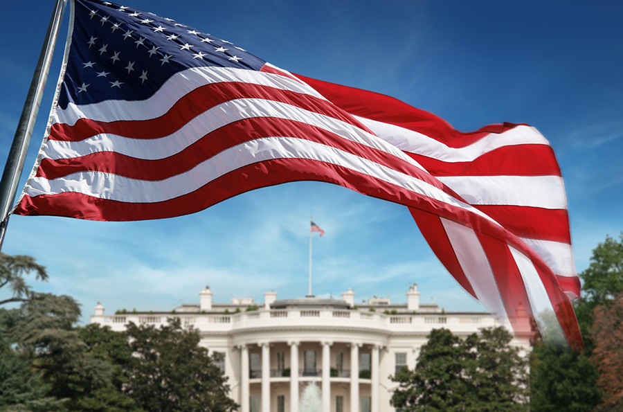 An American flag in front of the White House